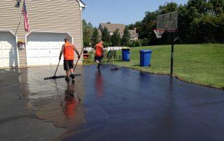 Men sealcoating driveway