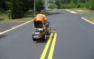man painting lines on road